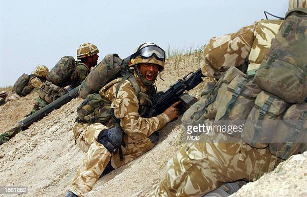 This image released by the British Royal Navy shows a soldier from the 1st Royal Regiment of Fusiliers giving the order to move over the berm as they...