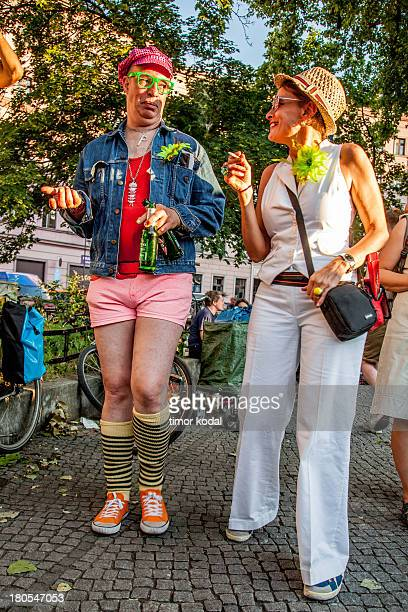 This image shows a man with striped stockings, hotpants, green glasses and a pink cap talking to a smoking woman in white wearing hat and glasses as...