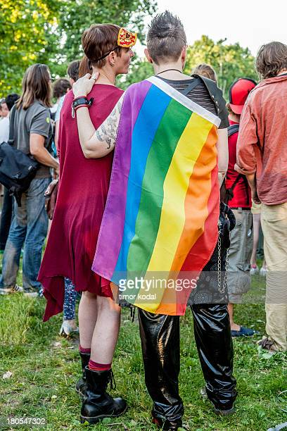 CONTENT] This image shows a tattooed man wearing latex pants and a rainbow flag with his hand on the shoulder of a girl with a red dress and a...