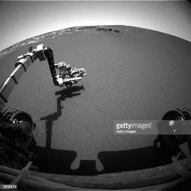 This image taken by the front hazardidentification camera onboard the Mars Exploration Rover Opportunity shows the rover's arm in its extended...