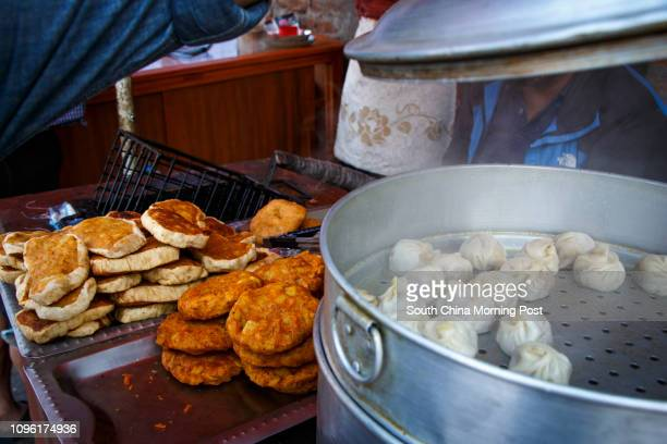 This image taken on 9 April shows street food momos Nepalese dumplings and bread pakodas Momos are a popular snack in Nepal and come steamed fried or...