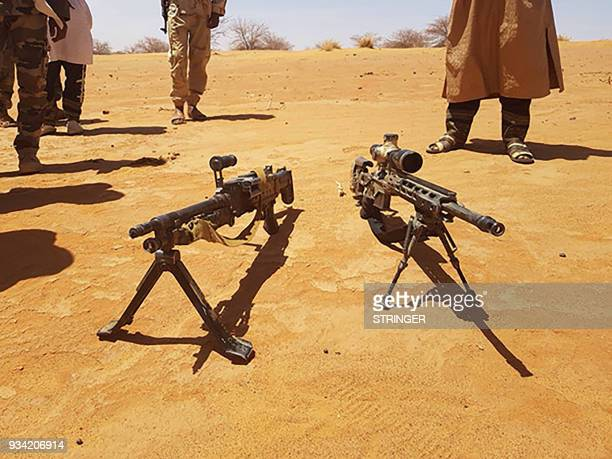 This image taken on on March 17 in Menaka Mali shows a M14 automatic rifle and a M240SLR machine gun which were recovered during an operation...