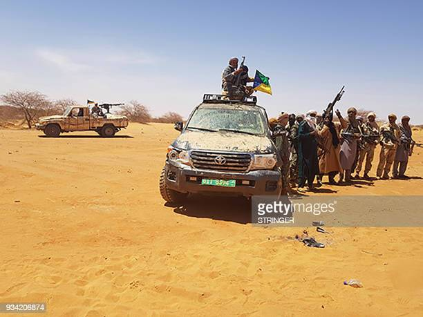 This image taken on on March 17 in Menaka Mali shows Azawad Salvation Movement militants flying their flag atop of an off road veichle recovered...