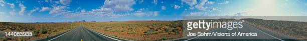 This is a 360 degree image of a fork in the road The rocks of Monument Valley are small in the background and there is desert foliage on all sides of...