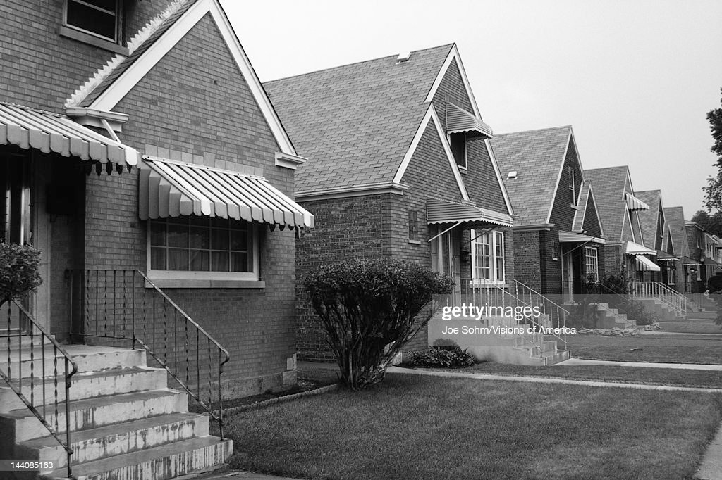 This is a black and white image of a row of single family houses, They are located on the south side of Chicago, They are brick houses with striped awnings over the front window and front door, There are steps and a thin railing leading up to the front door of each house, There are small front lawns in front of each house.