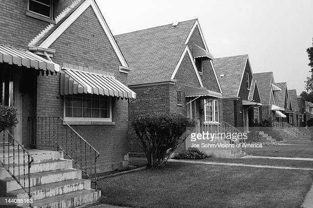 This is a black and white image of a row of single family houses They are located on the south side of Chicago They are brick houses with striped...