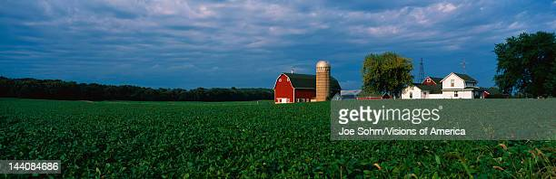 This is a farm with a silo and barn Directly behind it sits a white farmhouse It sits in the middle of a green farm field