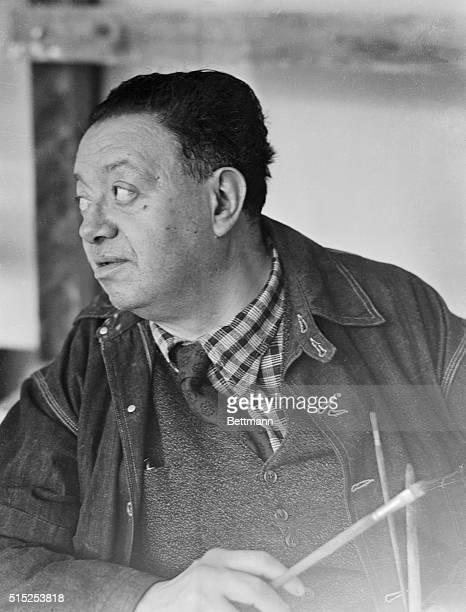 This is a head and shoulders photo of Mexican painter Diego Rivera as he looks to the side with a paintbrush in his hand
