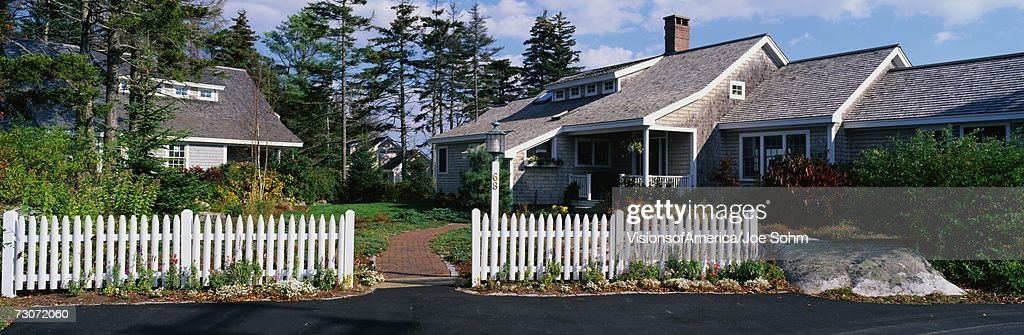 This is a lovely house with a typical suburban feeling. There is a white picket fence and a sidewalk leading up to the front door. The roof of the house slopes downward with trees in the background. : Stock Photo