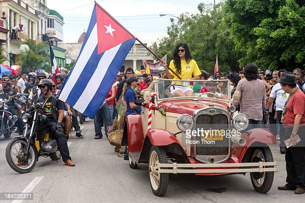 This is a parade for the cultural festival Romerias de Mayo in Holguin, Cuba. A woman holds the Cuban flag while standing in a Model A Ford. Alexis...