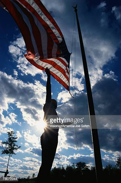 'This is a Park Ranger, raising the American flag on its flagpole. He is silhouetted, arm reaching up against a blue sky with clouds.'