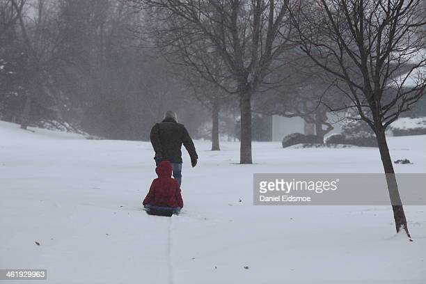 CONTENT] This is a photo of a father pulling his daughter on a sled during a winter storm in Bloomington Illinois
