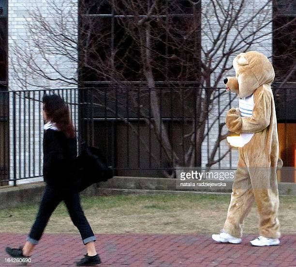 This is a photo of a person dressed in a bear suit handing out fliers near Northeastern University.