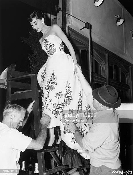 This is a photo of actress Audrey Hepburn standing halfway up a lifeguard's chair as she wears a flower-patterned dress. Two men are helping her.