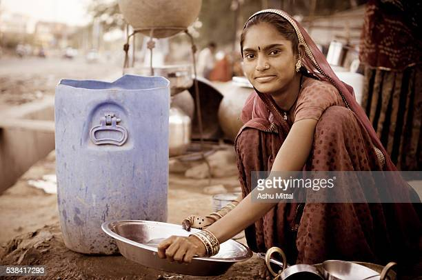 This is a photo of slum dweller woman in India She was washing the utensils by the roadside while her husband worked at a nearby construction site