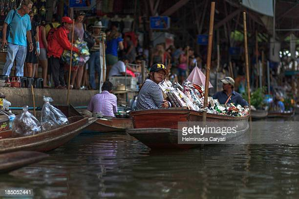 CONTENT] This is a picture of random people working and visiting floating marketBangkok Thailand