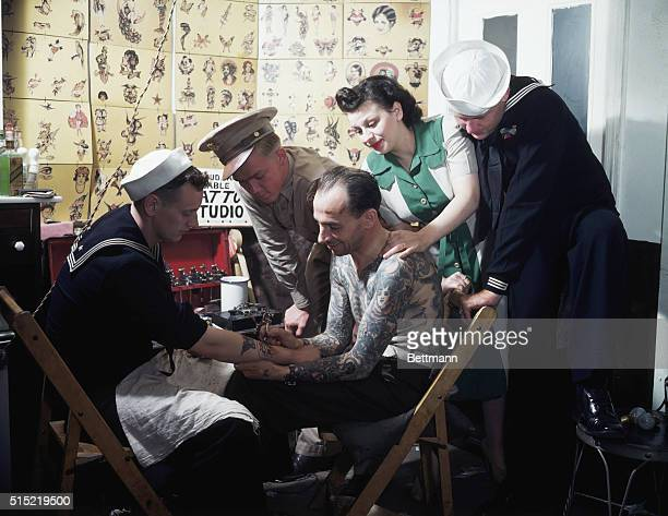 This is a sailor in the 1940s being tattoed by a tattoo artist that is himself elaborately tattooed over the top half of his body Ca 19401950