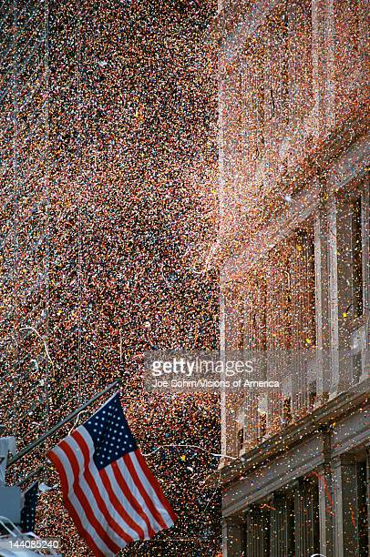 This is a shot of confetti and ticker tape falling like snow at the Ticker Tape Parade for the Desert Storm Victory An American flag is waving at the...
