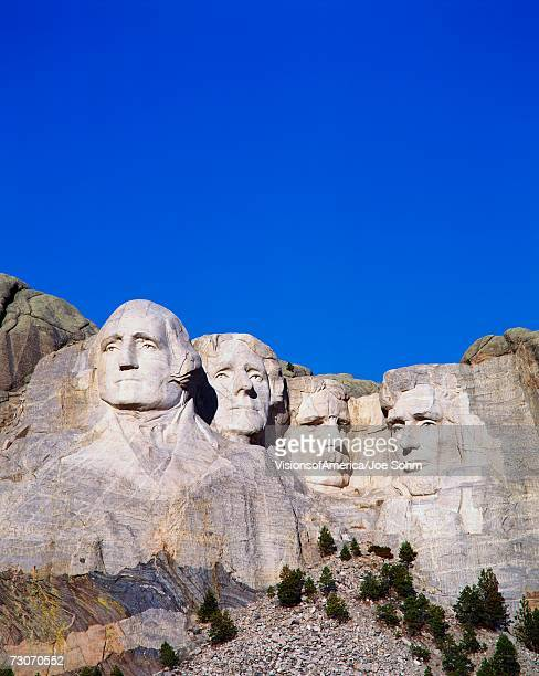 'This is a vertical image of Mount Rushmore National Monument showing the four faces of George Washington, Thomas Jefferson, Theodore Roosevelt, and Abraham Lincoln.'