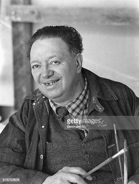 This is a waistup photo of Mexican Diego Rivera smiling as he reaches into an inner pocket of his jacket