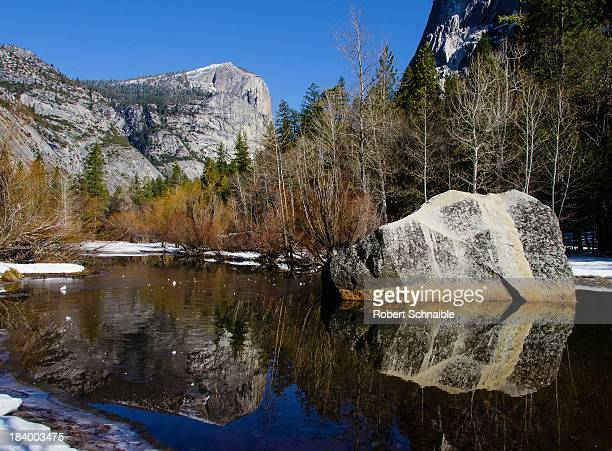 This is a winter view of Tenaya Creek located under the Yosemite landmark of Half Dome looking towards North Dome with reflections of stone and trees...