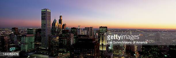 This is an aerial view of the skyline with the Sears Tower at sunset It is a summer evening and the lights of the city are on