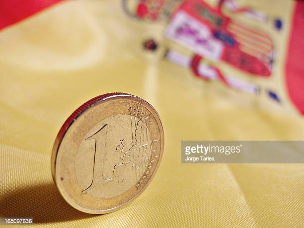 This is an Euro coin on a Spanish flag representing the future of Spain inside the Euro zone and the current crisis situation.