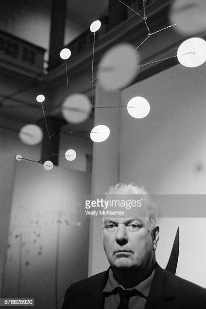 This is artist mobilist Alexander Calder posing midst his mobile exhibit at the Corcoran Gallery of Art in Washington DC | Location Corcoran Gallery...