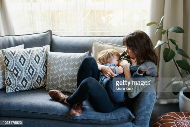this is how he prefers to fall asleep - young mom breastfeeding stock photos and pictures
