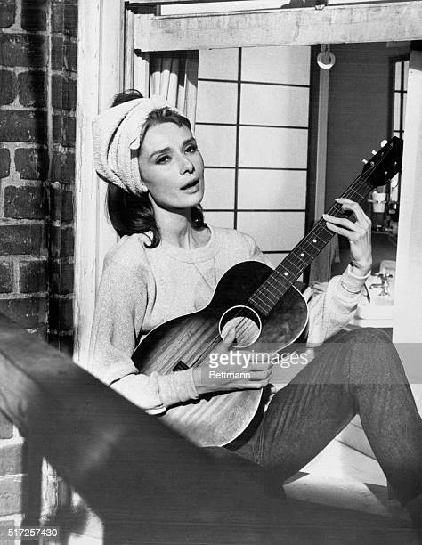 """This is not some Beatnik serenading her neighbors from the window of her """"pad."""" The wistful lass strumming the guitar is Audrey Hepburn, who is..."""