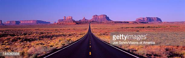 This is Route 163 that runs through the Navajo Indian Reservation The road runs up the middle and gets smaller into infinity The red rocks of...