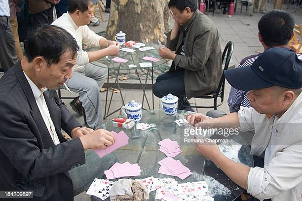 This is such a typically chinese situation - older men sitting amongst themselves in the park in the afternoon, playing cards ,smoking and drinking...