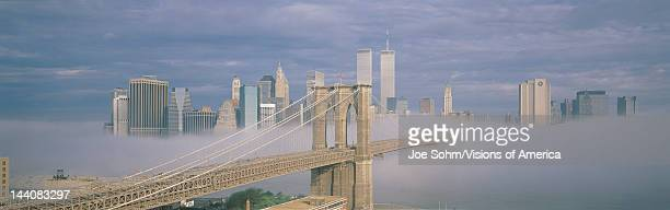 This is the Brooklyn Bridge over the East River with the Manhattan skyline behind it There is a morning fog enveloping the bridge and make it look...