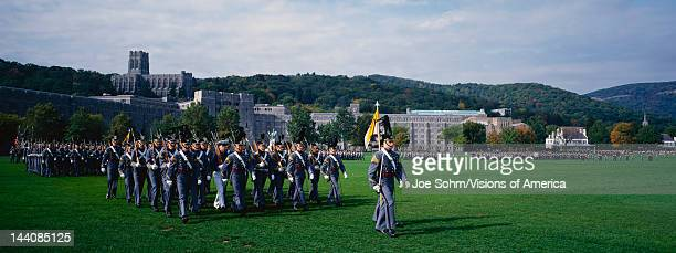 This is the exterior of the West Point Military Academy Marching are the Homecoming Parade of Cadets in grey uniforms and tall hats holding long guns