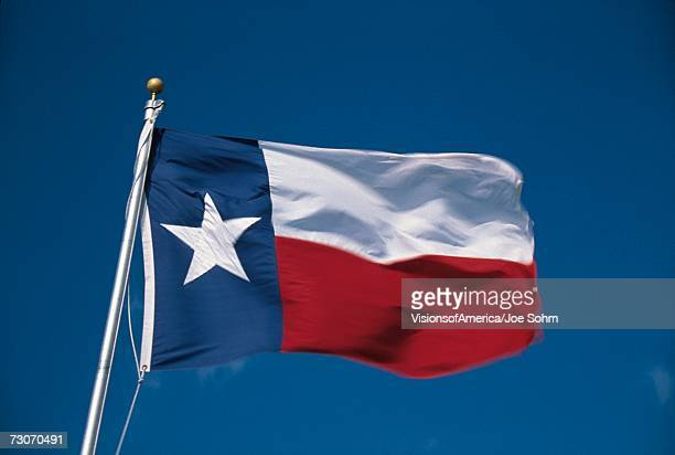 This is the State Flag flying in the wind. it is on a flagpole against a blue sky. There is a single white star on the left hand side against blue with a white stripe.