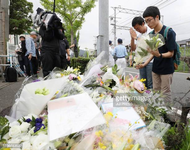 This July 19 2019 picture shows men praying for victims of a fire which hit the Kyoto Animation studio building the day before killing 33 people in...