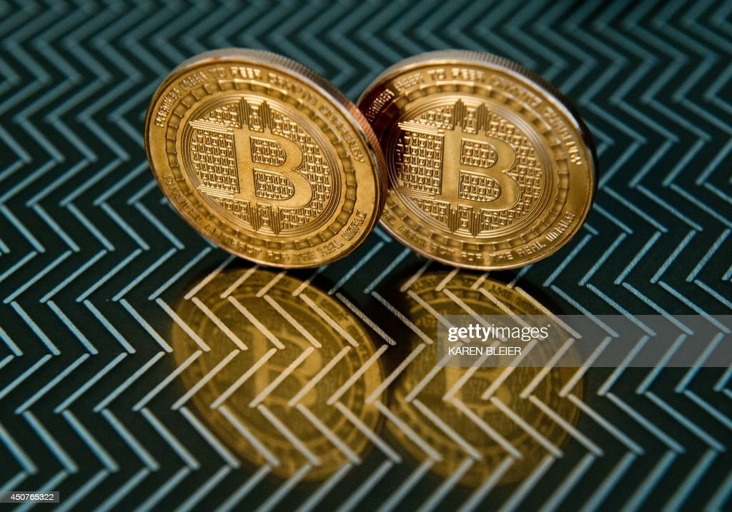This June 17, 2014 photo taken in Washington, DC shows bitcoin medals. Bitcoin uses peer-to-peer technology to operate with no central authority or banks; managing transactions and the issuing of bitcoins is carried out collectively by the network. AFP PHOTO / Karen BLEIER