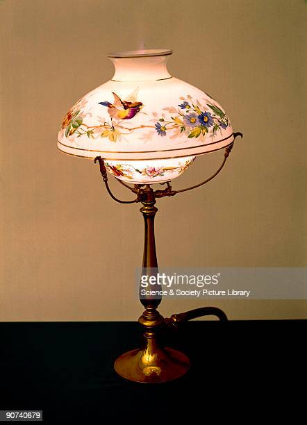 This lamp with a glass shade decorated with birds and flowers incorporates a 'London' governor for regulating the gas pressure and keeping the burner...