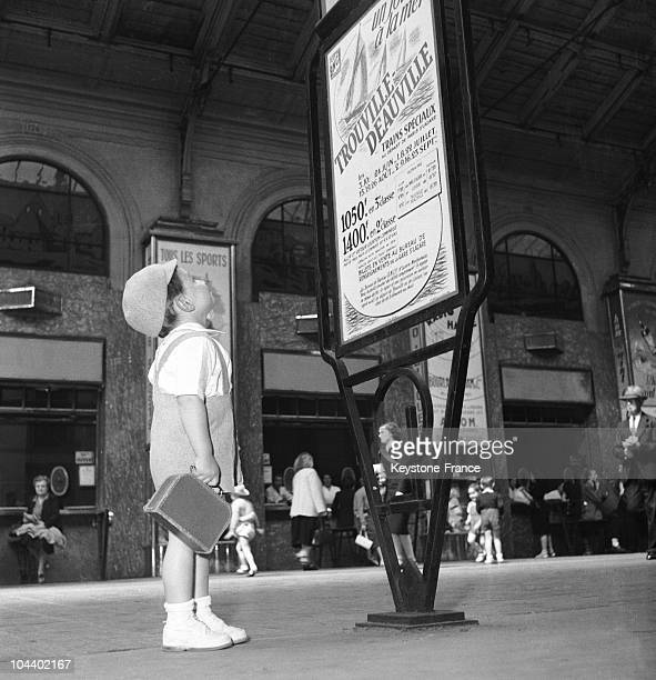 This little boy is studying a advertisement at the Saint-Lazare train station in Paris about the price of tickets to Trouville and Deauville