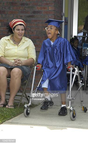 this little girl is so excited to receive her diploma she is dashing to the stage with the assistance of her walker. - cerebrum stock pictures, royalty-free photos & images