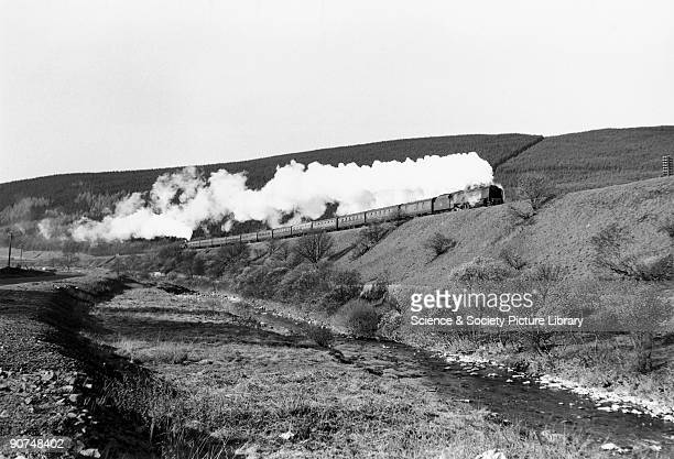 This locomotive No 46220 climbs the southern slope of Beattock Bank with the assistance of a banking engine while the Elvan Water flows in the...