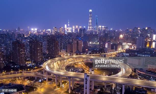 TOPSHOT This long exposure image shows traffic on the Nanpu Bridge in front of the skyline of Shanghai on February 14 ahead of the Lunar New Year The...