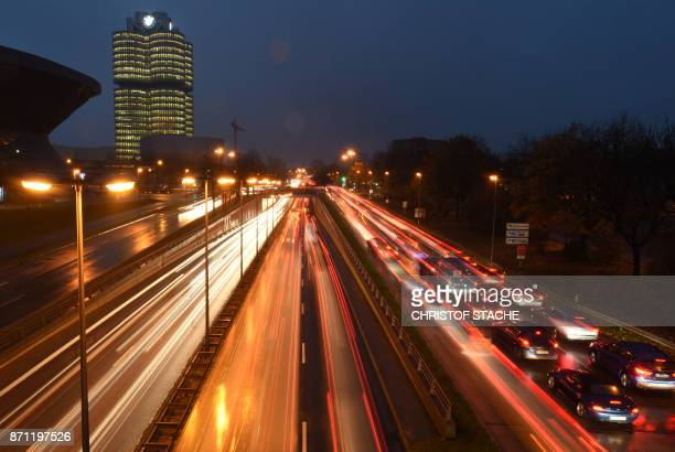 This long exposure photo shows early morning traffic making its way past the headquarters of German car maker BMW on the motorway in Munich, southern...
