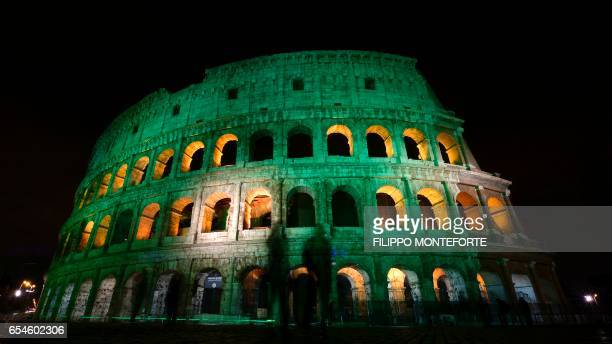 TOPSHOT This long exposure photo taken on March 17 2017 in Rome shows the Colosseum illuminated in green for the St Patrick's Day holiday / AFP PHOTO...