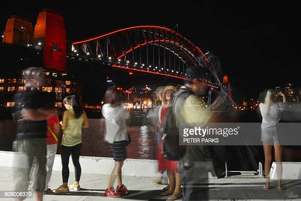This long exposure photograph shows Chinese tourists taking photos in front of Sydney Harbour Bridge which is lit up red to welcome in the Lunar New...