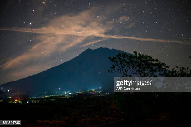 This long exposure photograph shows Mount Agung under a starry sky as seen from Kubu in Karangasem on the Indonesian resort island of Bali on...
