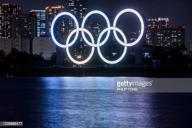 This long exposure picture shows the lit Olympic rings at the waterfront of Odaiba in Tokyo on December 1, 2020.