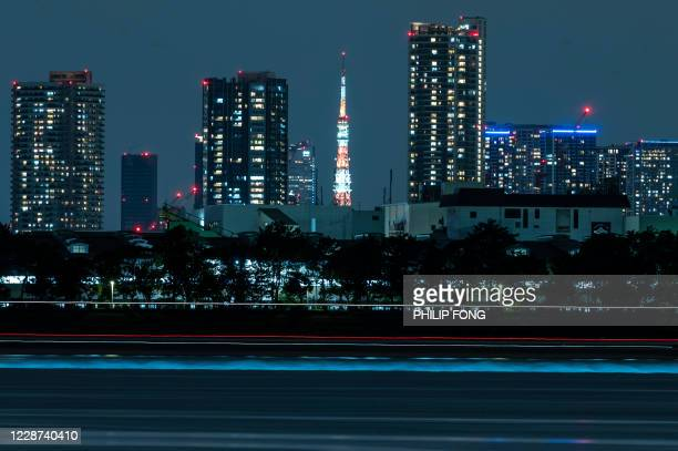 This long exposure picture shows the Tokyo Tower lit up alongside the skyline of the city in Tokyo on September 27, 2020.