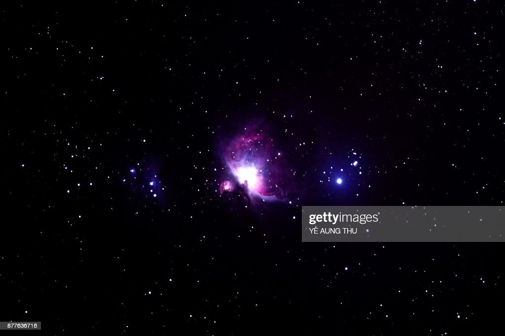 This long exposure picture taken late on November 22, 2017 shows the Orion Nebula (C), a diffuse nebula situated in the Milky Way, seen from Wundwin, near the Myanmar city of Mandalay. /