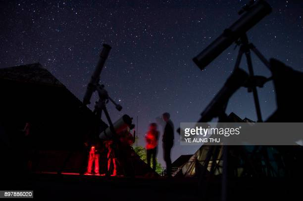 This long exposure picture taken on December 23 2017 shows members of the Myanmar Astronomy and Science Enthusiasts preparing a telescope to take...